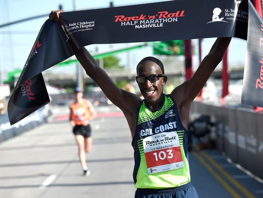 Roosevelt Cook of Hesperia, Calif., celebrates his win in the men's half-marathon.