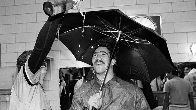 In this Sept. 25, 1983, file photo, Baltimore Orioles pitcher Sammy Stewart, right, uses an umbrella to keep dry as teammate Bill Swaggerty pours a beverage during their victory celebration after defeating the Milwaukee Brewers to win the American League Eastern Division title in Milwaukee, Wis. Stewart died March 3 in Hendersonville.