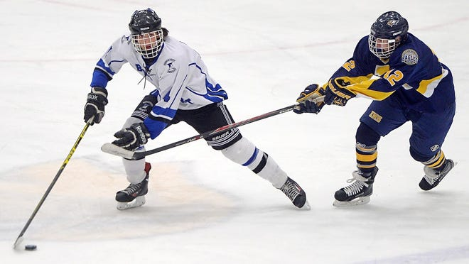Brockport's Mitchell Henshaw, left, skates the puck away from Irondequoit's Michael Coholan.