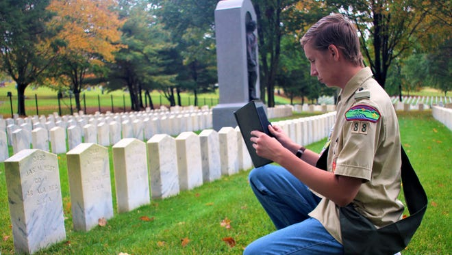 Eagle Scout candidate Jack Christiansen photographs gravestones at Woodlawn National Cemetery for inclusion on the website FindAGrave.com.