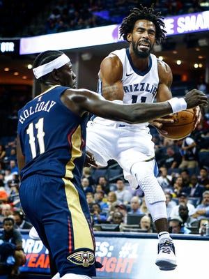 Grizzlies guard Mike Conley (right) is fouled by Pelicans defender Jrue Holiday (left) while driving the lane.