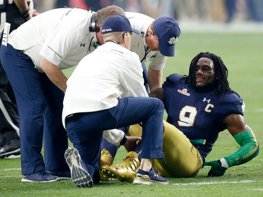 FILE - In this Jan. 1, 2016, file photo, Notre Dame linebacker Jaylon Smith (9) is attended to after a knee injury during the first half of the Fiesta Bowl NCAA college football game against Ohio State in Glendale, Ariz. Smith went early in the second round of the NFL draft to the Dallas Cowboys despite the injury. And while the consensus is he'll have to wait until 2017 to make his NFL debut after tearing two ligaments and sustaining nerve damage in his left knee, Smith begs to differ after the Cowboys took him with the 34th overall pick Friday night, April 29. (AP Photo/Rick Scuteri, File)