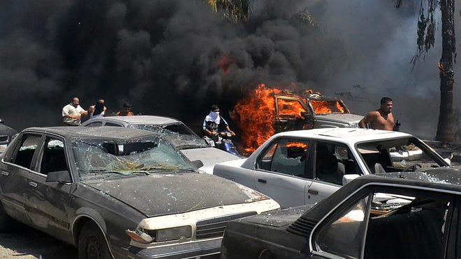 Lebanese men run between burning cars at the site of an explosion outside a mosque in the Northern city of Tripoli, Lebanon, Friday Aug. 23, 2013.  Lebanon's official news agency says dozens of people have been killed by twin explosions outside two Sunni mosques in a northern city. The explosions in Tripoli come amid rising tensions in Lebanon resulting from Syria's civil war, which has sharply polarized the country along sectarian lines and between supporters and opponents of the regime of President Bashar Assad. Tripoli has previously seen clashes between Sunnis and Alawites, a Shiite offshoot sect to which Assad belongs.(AP Photo) ORG XMIT: BEI113