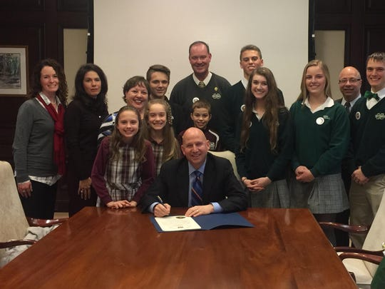 Delaware Gov. Jack Markell is signing a proclamation honoring Catholic schools as Saint Mark's High School students look on.