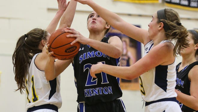 Simon Kenton's Morgan Stamper takes the ball to the basket between two Notre Dame defenders during the first quarter of their game at Notre Dame, Wednesday, December 7, 2016.