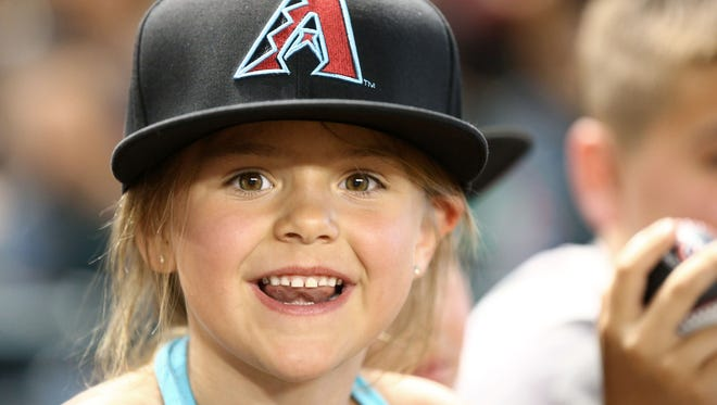 Diamondbacks fan Atalie Davis, age 5 from Montana hangs out near the Arizona dugout on opening day on Mar. 29, 2018 at Chase Field in Phoenix, Ariz.