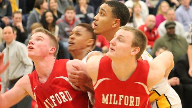 Walnut Hills freshman Omari Peek tries to sneak in for a rebound behind Milford junior Jack Engelman (4) and senior Will Hannah on Feb. 13.