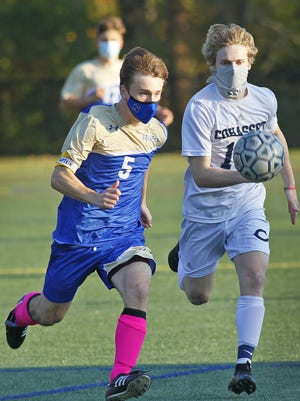 Norwell's captain Charles Pesko (#5)  tries to outrun Cohasset's Jack Elliot (#10) on Thursday, Oct. 22, 2020.