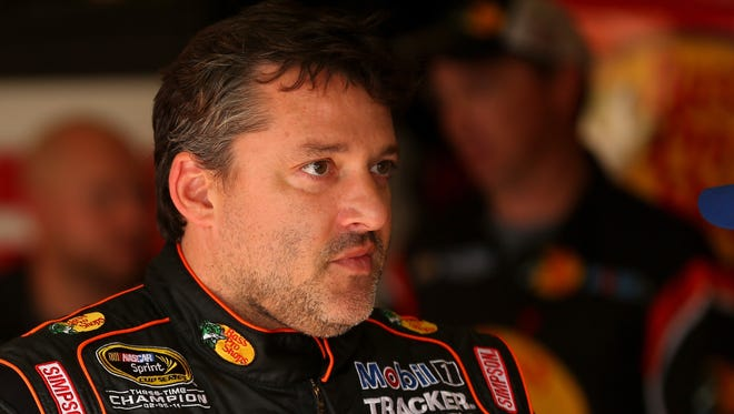 Tony Stewart, driver of the #14 Bass Pro Shops / Mobil 1 Chevrolet, stands in the garage area during practice for the NASCAR Sprint Cup Series Oral-B USA 500 at Atlanta Motor Speedway on August 30, 2014 in Hampton, Georgia.