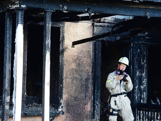 Maryland State Fire Marshal Carl Witmer looks at photos