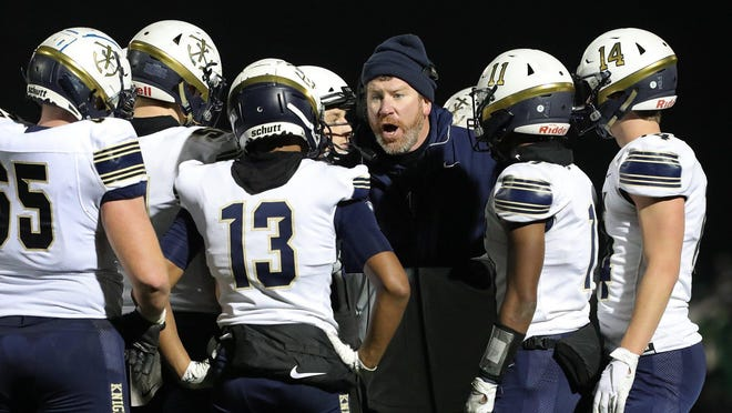 Hoban football coach Tim Tyrrell goes over the game plan during a Division II regional semifinal against Mayfield on Nov. 15, 2019, in Macedonia.