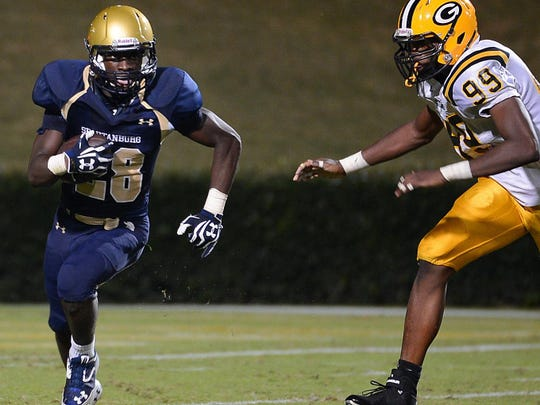 Spartanburg's Tavien Feaster (28) takes the ball downfield against Greenwood's Brandon Henderson (99) during a 2013 game.