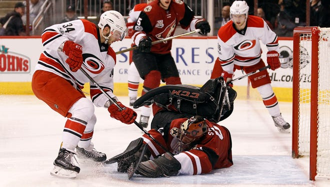Arizona Coyotes goalie Mike Smith, center, makes a diving save on the shot by Carolina Hurricanes' Phillip Di Giuseppe (34) during the first period of an NHL hockey game, Sunday, March 5, 2017, in Glendale, Ariz.