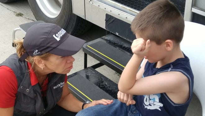 Susan Mangicaro, of Naples, executive director of global response for Heart to Heart International, tends to a victim of Hurricane Harvey in Victoria, Texas. Mangicaro's work has taken her around the world to help provide medical care at disaster sites including Haiti, the Philippines and Liberia.