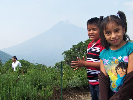 A couple of Guatemalan youngsters in front of Agua, one of several volcanoes in the Antigua area and near Fuego, which erupted this week.