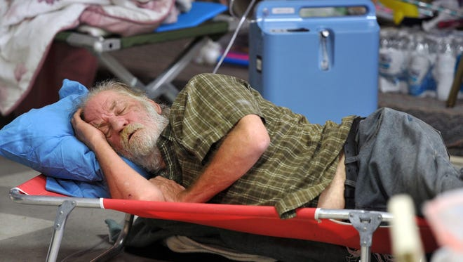 Evacuee Robert Jones sleeps at The Moose Lodge in Clearlake Oaks, Calif., while the Rocky fire burns on Tuesday, Aug. 4, 2015.