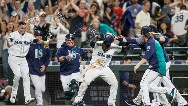 Seattle Mariners, including Jean Segura, center, Edwin Diaz, left, Carlos Ruiz, third from left, and Gordon Beckham, right front, celebrate after Segura scored on a wild pitch in the ninth inning of Saturday's game against Oakland.