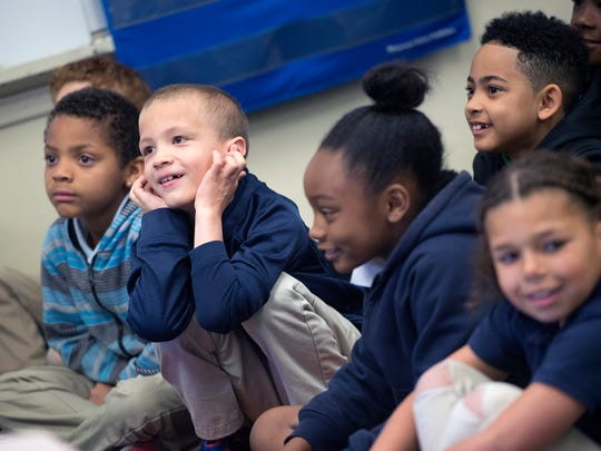 Second-graders smile while William Penn Senior High School basketball coach and educator Clovis Gallon reads a story at Devers K-8 school in York on Monday as part of an annual event promoting reading and responsibility.