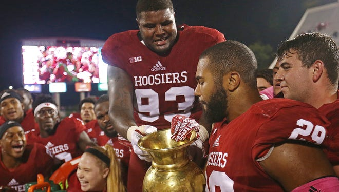 Indiana Hoosiers defensive lineman Ralph Green III (93) holds the brass spittoon for Indiana Hoosiers linebacker Dawson Fletcher (29) to spit into after defeating Michigan State, Bloomington, Ind., Saturday, October 1, 2016. The Hoosiers beat the Spartans in overtime, 24-21.