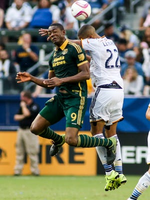 Portland Timbers forward Fanendo Adi, left, and Los Angeles Galaxy defender Leonardo battle for a head ball in the second half of an MLS soccer game in Carson, Calif., Sunday, Oct. 18, 2015. The Timbers won 5-2. (AP Photo/Ringo H.W. Chiu)