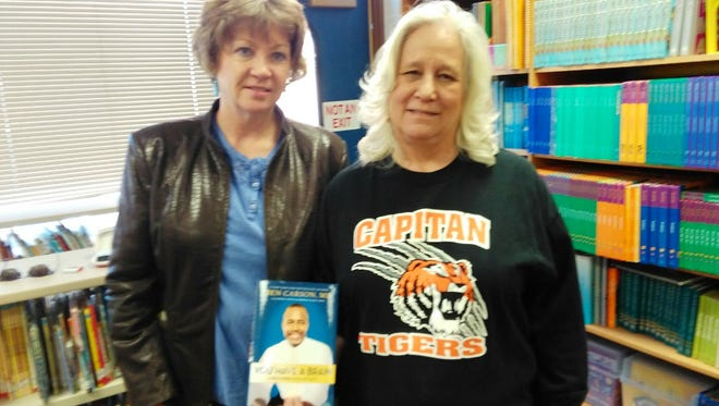 Betty Roberts from FRWLC presents books to a staff member at the Capitan school library.