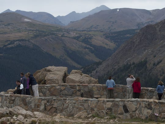 Visitors take in the views from the Forest Canyon overlook