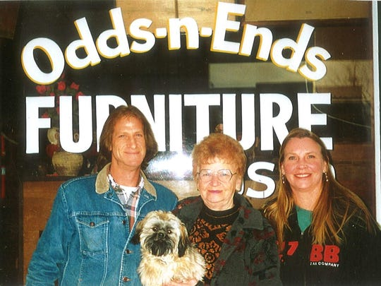 "Curtis Ramsay, Ann Ramsey, holding Corky, and Cathy stand in this undated photo in front of the Odds n Ends Shop. ""That's when mom skill had red hair,"" Cathy joked."