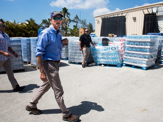 Gov. Rick Scott walks through a distribution site outside