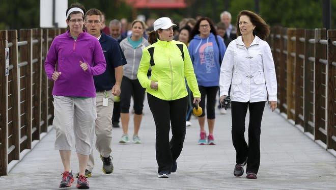 Sandy Campbell, left, Tim Rice, Betsy Rozelle and Shawn Boogaard walk along the Trestle Trail near Fritse Park on June 13 during the Weight of the Fox Valley's Passport to Active Living kickoff event in Fox Crossing.