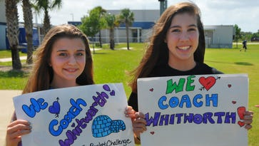 A former teacher at the school, Jason Whitworth, was  diagnosed with ALS in 2011. Nicole Conde and Allie Kellner hold up signs for the event.