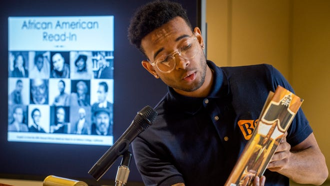 """UT student Kendall Whiteside reads Lesa Cline-Ransome's """"Just a Lucky So and So: The Story of Louis Armstrong"""" during the UT Center for Children's and Young Adult Literature's African American Read-In held at Hodges Library on UT's campus on Friday, Feb. 24, 2017."""