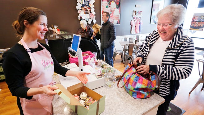 Owner Emily A. Goertemoeller with a selection of cupcakes for Denise Nichols Friday, November 17, 2017, at Gigi's Cupcakes, 170 South Creasy Lane #1710 in Lafayette. Nichols was buying cupcakes for her grandson's birthday.