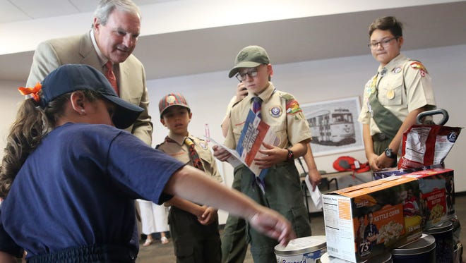 """El Paso Mayor Dee Margo looks on as popcorn choices are explained to him by Scout Booth, left, and other representatives of local Cub and Boy Scouts during a ceremonial first sale of their popcorn selling season Monday at City Hall. Margo ordered two types of popcorn from the group. They will be selling 10 varieties of popcorn around town Saturday through Nov. 5. """"The coolest thing about our sale is that the Scouts have an opportunity to learn some real-life skills like setting goals and salesmanship and communication and other variables like that,"""" said Mario Perez, Scout executive and CEO of the Boy Scouts of America Yucca Council. Aside from El Paso, the Scouts will be selling throughout the council's seven county area, which includes five counties in Southern New Mexico and two in West Texas. A military donation program allows people to support scouting with a $25 donation. The popcorn company will then ship popcorn to military personnel serving oversees, Perez said."""