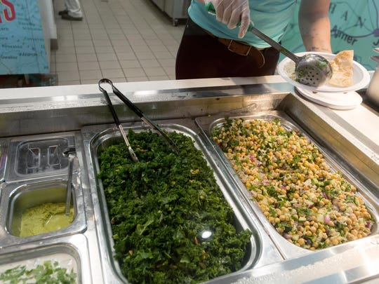 A Mela restaurant employee scoops chick pea salad in the Highsmith University Union food court.