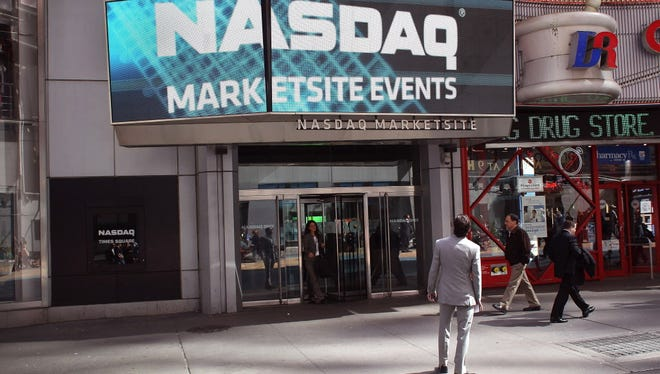 Pedestrians walk past the Nasdaq stock market at Times Square on March 14, 2012, in New York City.