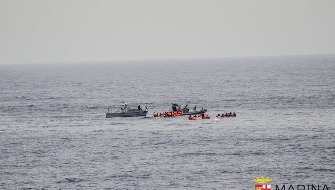 Rescuers help migrants to board rubber dinghies on May 27, 2016, before towing them to the Italian navy ship Vega, after the boat they were aboard sunk in the  Mediterranean Sea, off the Libyan coast, Friday. The Italian navy says it has saved 135 migrants and recovered 45 bodies in the Mediterranean.