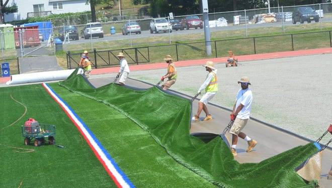 Workers move a panel of new synthetic turf into place July 29, 2015, at Millburn High School's Dr. Keith A. Neigel Field.