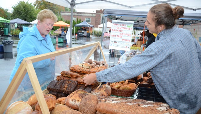 Edie DeVries takes a look at some items being sold by Chris Scott last October at the Glen Rock Farmer's Market.