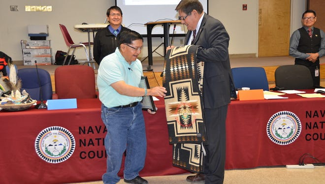 Former Navajo Nation Council Delegate Peterson B. Yazzie, left, receives a blanket for his service on the council from Speaker LoRenzo Bates on April 13 in Window Rock, Ariz.