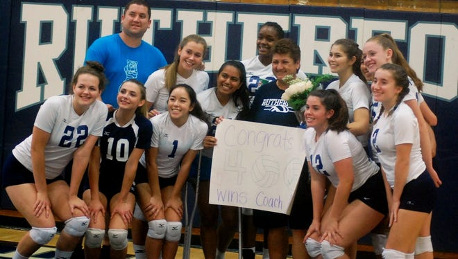 Rutherford girls volleyball players and assistant coaches surround Helen Antzoulides (center) after she won her 400th career game with the Lady Bulldogs.