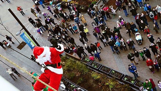 Santa rappels down the Center Ithaca building.