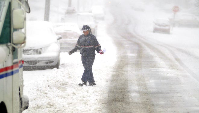 A U.S. Postal Service mail carrier walks during a snowstorm on Third Street in Blakely, Pa., Friday, March 2, 2018. A relentless nor'easter pounded the Atlantic coast with hurricane-force winds and sideways-blown rain and snow Friday, flooding streets, grounding flights, stopping trains and leaving hundreds of thousands of people without power from North Carolina to Maine. (Butch Comegys/The Times-Tribune via AP)