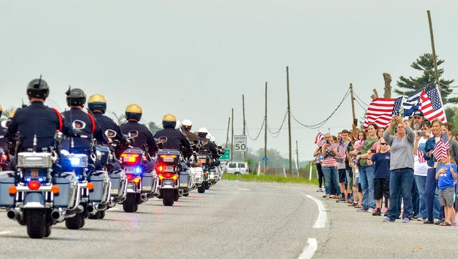 Several dozen people line US 41 in Farmersburg, Ind., as Terre Haute Police Officer Rob Pitts' funeral procession passed through town on its way from Hulman Center in Terre Haute, Ind., Wednesday, May 9, 2018 to Center Ridge Cemetery in Sullivan, Ind. Pitts, a 16-year veteran of the Terre Haute Police Department, died following a May 4 shootout with a homicide suspect.  (Austen Leake/The Tribune-Star via AP)