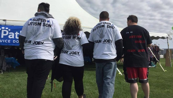 """Joshua Wallace, the """"Super Autism Son"""" (left), walks alongside his parents. Their team went with a superhero theme Sunday morning."""