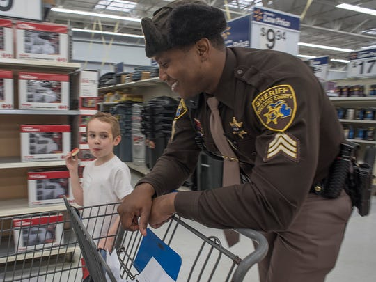 Cody Riter eats a cookie and lets Lt. Leslie Whitfield push the cart in this 2017 photo during a Shop with a Cop event.