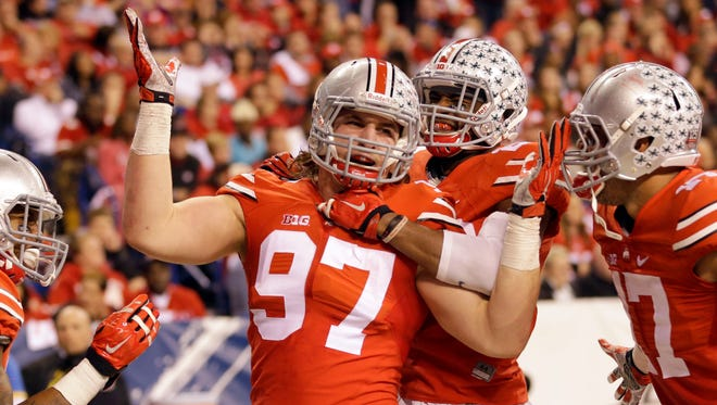 Ohio State defensive lineman Joey Bosa (97) is congratulated by teammates after recovering a fumble and running it back for a touchdown against Wisconsin on Dec. 6, 2014, in Indianapolis.