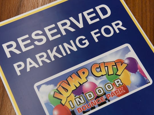 Signs are prepared to mark parking spaces at the new Jump City indoor inflatable park Wednesday, April 4, in St. Cloud.