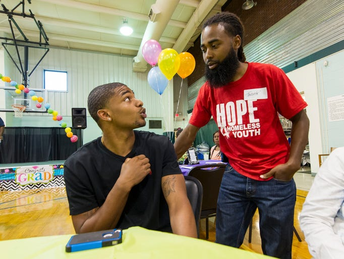 Christian Jones, left, graduated from Shortridge High School. He is talking with his mentor, Tavonte Hughes. About 20 new high school graduates celebrated their accomplishment, Saturday, June 14, 2014, at Post Road Christian Church. Through Outreach, Inc, a group that reaches out to homeless young adults, the students received mentoring and support.