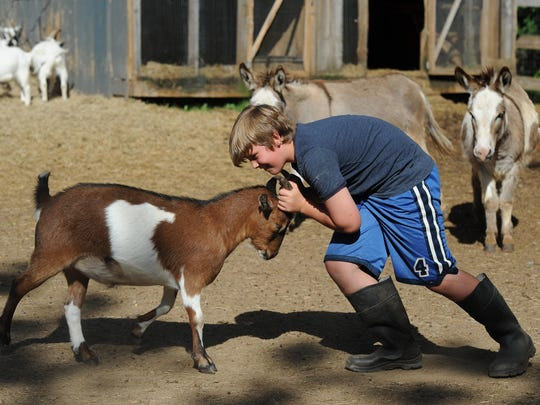 Izzie's Pond volunteer Bennett Van Every plays with a goat Friday, May 22, 2015. Izzie's Pond is a waterfowl and rescue sanctuary in Simpsonville.