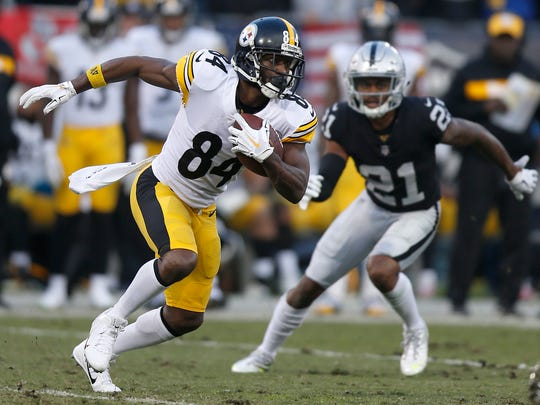 """File-This Dec. 9, 218, file photo shows Pittsburgh Steelers wide receiver Antonio Brown (84) running against Oakland Raiders cornerback Gareon Conley (21) during the second half of an NFL football game in Oakland, Calif. Brown is modifying his jersey, using a marker to add an """"s"""" to the end of his last name. Safety Sean Davis is mulling a present or two to Cleveland quarterback Baker Mayfield, promising to send the rookie """"a little something something"""" if the Browns can beat the Baltimore Ravens on Sunday and open the door for the Steelers to win a third straight AFC North title.  (AP Photo/D. Ross Cameron, File)"""
